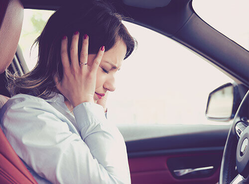 A woman tries to protect herself from noise in the car.